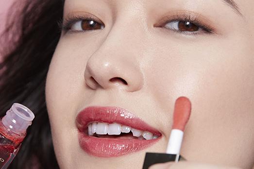 Una mujer poniéndose lápiz de labios de Clarins