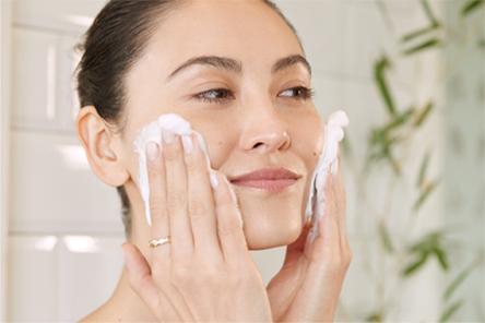 Mujer aplicándose un tratamiento facial Clarins